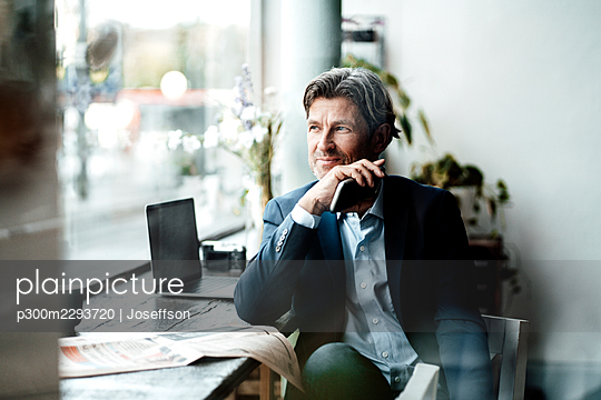 Smiling businessman holding smart phone looking through window while sitting at table in cafe - p300m2293720 by Joseffson