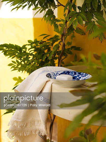 Soap on blue and white bowl with towel in Spanish courtyard - p349m2167726 by Polly Wreford