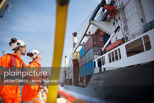 Workers on tug boat overlooking ship - p429m726932f by Monty Rakusen