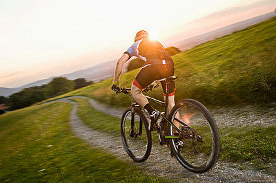 Mountain biker riding on a trail at sunset - p1026m786143f by Robert Niedring