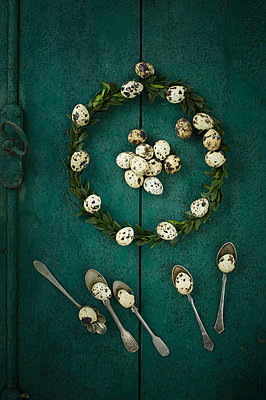 Box tree wreath, quail eggs and silver tea spoons on green wood - p300m1175899 by Achim Sass