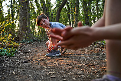 Boy tying his shoelace while looking at sister in forest - p300m2197339 by Stefanie Aumiller