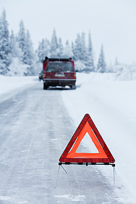 A warning triangle on a country road in the winter Sweden. - p31217864f by Jakob Fridholm
