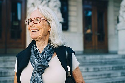 Smiling senior woman looking away while exploring city - p426m2183312 by Maskot
