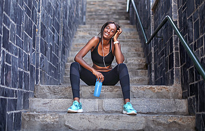 Young female runner listening to earphones taking a break on city stairway, portrait - p924m2090591 by Bean Creative