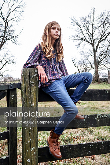Girl sitting on wooden fence - p1019m2142882 by Stephen Carroll
