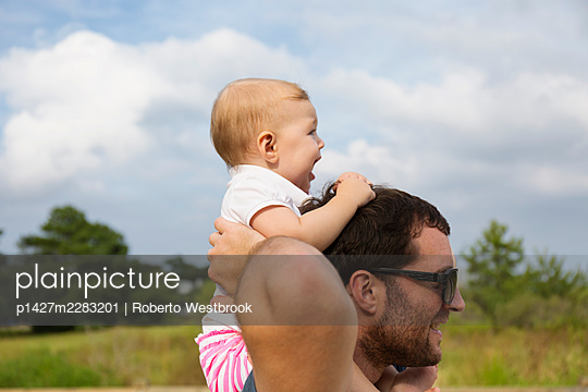 Mid adult man carrying baby daughter on shoulders - p1427m2283201 by Roberto Westbrook