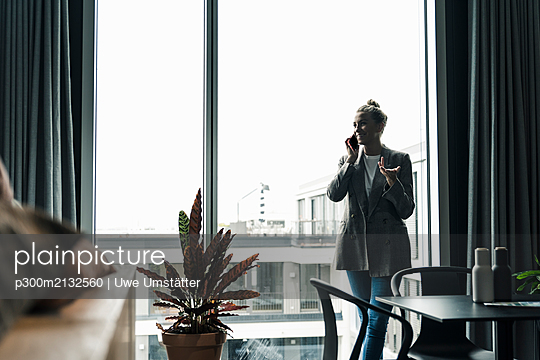 Smiling businesswoman on cell phone standing at the window in office - p300m2132560 by Uwe Umstätter