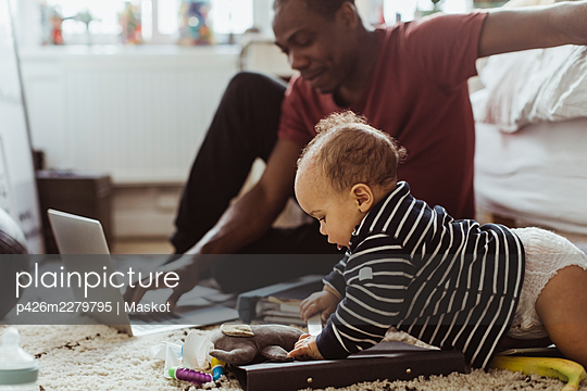 Male toddler playing with toys by father using laptop in bedroom - p426m2279795 by Maskot