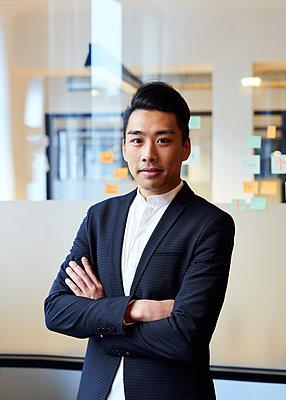 Asiatischer Mann im Büro mit verschränkten Armen - p1124m1181490 von Willing-Holtz