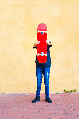 Schoolboy holding skateboard while standing on footpath against wall - p1166m2068031 by Cavan Images