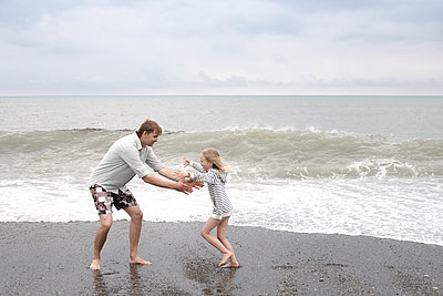 Father playing with his daughter on the beach - p300m2114003 by Ekaterina Yakunina