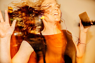 Close-up of cheerful woman dancing while listening music at home - p300m2206746 by Jan Tepass