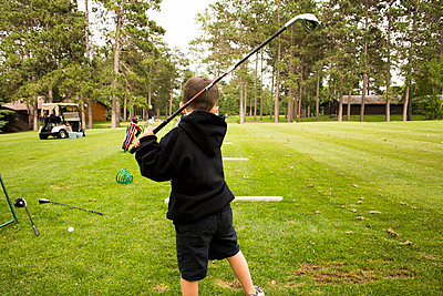 Mixed race boy swinging golf club - p555m1303601 by Adam Hester