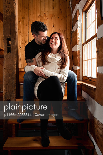 Happy couple sitting on stairs together inside rustic log cabin. - p1166m2255814 by Cavan Images