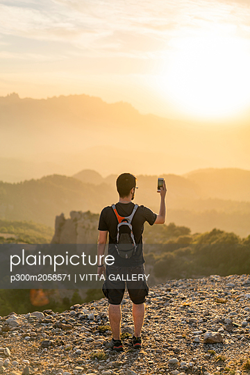 Spain, Barcelona, Natural Park of Sant Llorenc, man hiking and taking a picture of the view at sunset - p300m2058571 by VITTA GALLERY