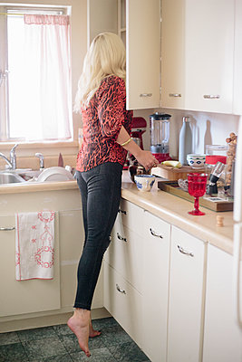 Blonde woman standing in a kitchen on tiptoes looking in a cupboard. - p1100m1080241 by Mint Images