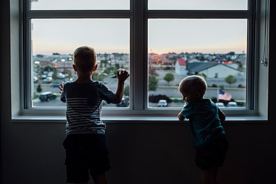 Rear view of brothers looking through window while standing at home during sunset - p1166m1519010 by Cavan Images