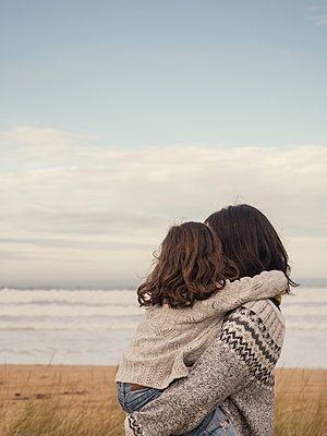 mother and daughter hugging on the beach - p1522m2144999 by Almag