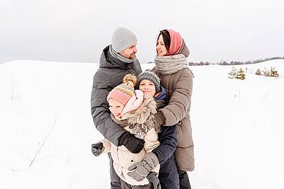 Family enjoying vacation on snow covered landscape against sky - p300m2251170 by Ekaterina Yakunina