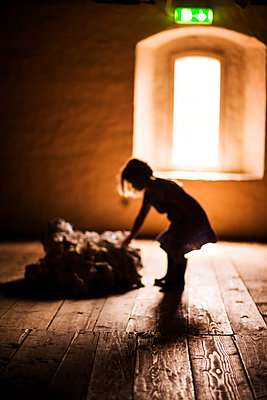 Silhouette of girl standing on wooden floor - p312m1228955 by Peter Rutherhagen