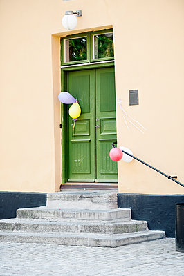 Green door with balloons - p312m1229389 by Rebecca Wallin