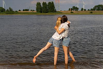 Beste Freundinnen umarmen sich am Strand - p432m2264006 von mia takahara