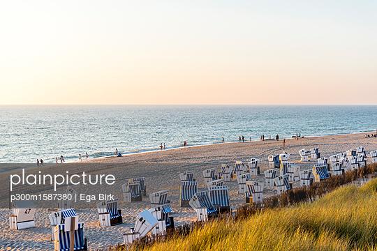 Germany, Schleswig-Holstein, Sylt, beach and empty hooded beach chairs at sunset - p300m1587380 von Ega Birk
