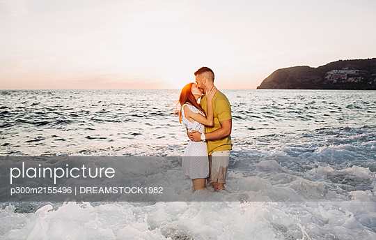 Young couple kissing each other at the beach during sunset - p300m2155496 by DREAMSTOCK1982