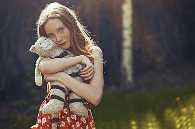Portrait serene tween girl with stuffed animal in park - p1023m2088089 by Arman Zhenikeyev