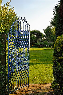 Open, blue iron gate showing view of expansive garden - p1183m997684 by Miebach, Bärbel