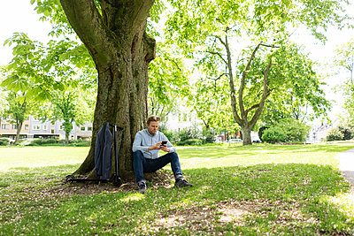 Businessman with E-Scooter leaning against tree trunk at city park using smartphone - p300m2114548 by Joseffson