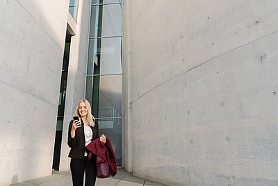 Blond businesswoman using smartphone in the background modern buildings - p300m2154510 by Hernandez and Sorokina