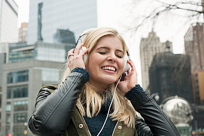 Young woman smiling while listening music in city - p300m2240038 by LOUIS CHRISTIAN