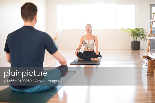 A girl and guy in a one on one yoga session. - p1166m2192062 by Cavan Images