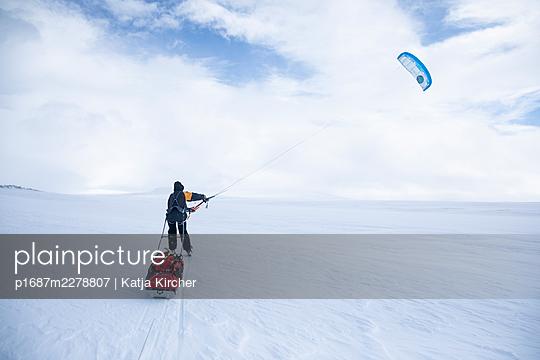 Man using a kite on a skiing trip in a vast snowy landscape - p1687m2278807 by Katja Kircher
