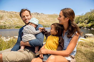 Family with baby on the lakefront - p1355m1574513 by Tomasrodriguez