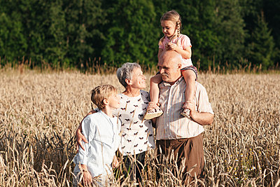 Family portrait of grandparents with their grandchildren in an oat field - p300m2143891 by Ekaterina Yakunina