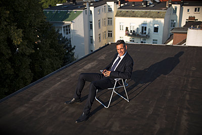 Businessman on roof - p341m2008624 by Mikesch