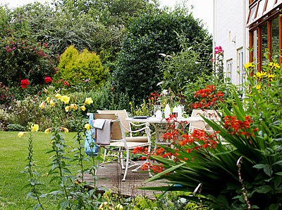 Garden furniture on patio with flowers in bloom  - p349m789660 by Brent Darby
