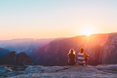USA, California, Yosemite National Park, Taft Point, Man and woman watching sunset in mountains - p352m1350134 by Eija Huhtikorpi