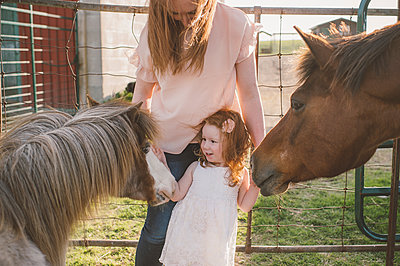 Mother and daughter petting pony in farm - p924m2039565 by Jenn Austin-Driver (Photography)