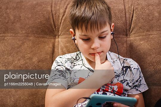 Teenager in headphones looks at phone screen - p1166m2255048 by Cavan Images