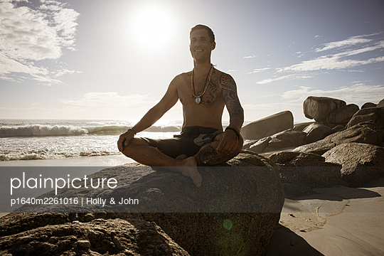Man practises meditation on the beach in the sunshine - p1640m2261016 by Holly & John