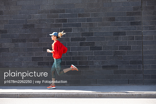 Woman jogging in Hamburg - p1678m2262250 by vey Fotoproduction