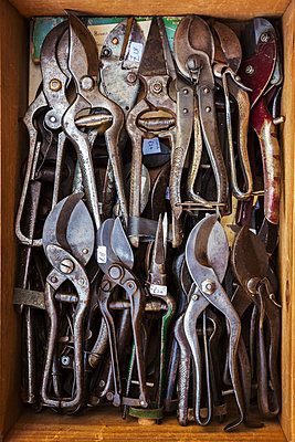 Overhead view of a box of old rusty worn metal shears, tin snips and pliers in a workshop. - p1100m1450994 by Mint Images
