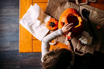 Overhead view of girl making jack o' lantern on table at home - p1166m2001364 by Cavan Images