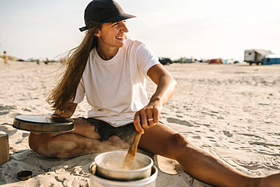 Smiling woman cooking on beach - p312m2217072 by Stina Gränfors