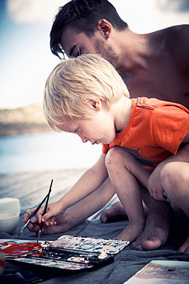 Boy painting with brother on jetty - p528m1075458f by Dan Lepp