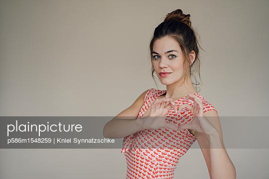 Junge Frau formt mit den Händen ein Herz - p586m1548259 von Kniel Synnatzschke
